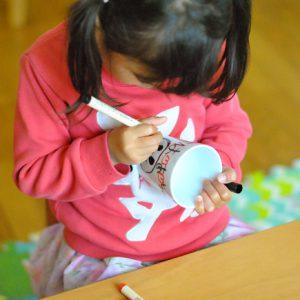 女の子がマグカップに絵を書いている